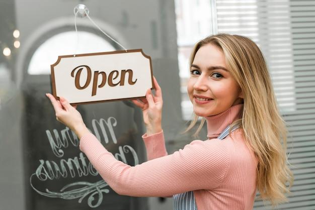 Giovane donna bionda che appende un'etichetta aperta sull'entrata della porta