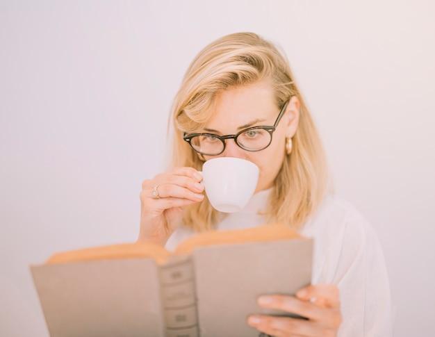 Giovane donna bionda che beve il caffè mentre leggendo il libro contro fondo bianco