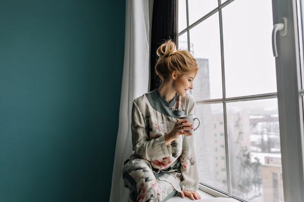 Giovane donna bionda che beve tè, caffè e guardando attraverso la grande finestra, felice, buongiorno a casa. indossare pigiami di seta con fiori. parete turchese