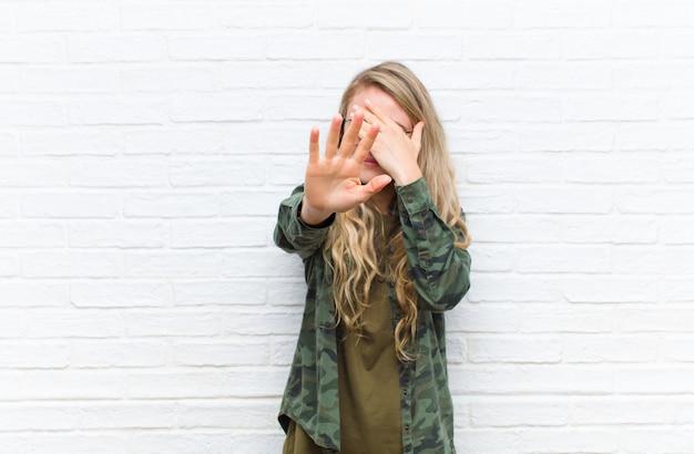 Giovane donna bionda che copre il viso con la mano e mettendo l'altra mano in alto per fermare la fotocamera, rifiutando foto o immagini su sfondo di muro di mattoni