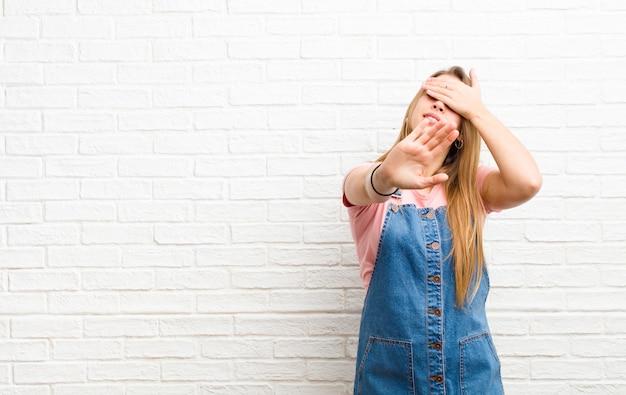 Giovane donna bionda che copre il viso con la mano e mettendo l'altra mano in alto per fermarsi, rifiutando foto o immagini contro il muro di mattoni