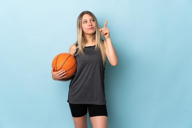 Giovane donna bionda che gioca pallacanestro isolata sulla parete blu