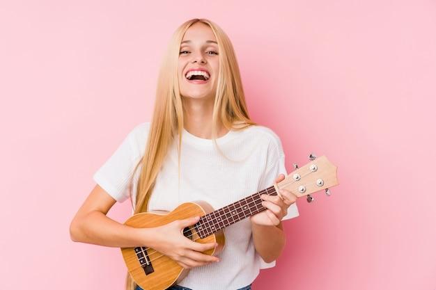 Giovane donna bionda che gioca ukelele in una parete