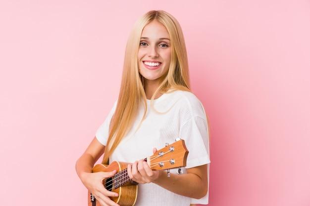 Giovane donna bionda che gioca ukelele isolato in una parete