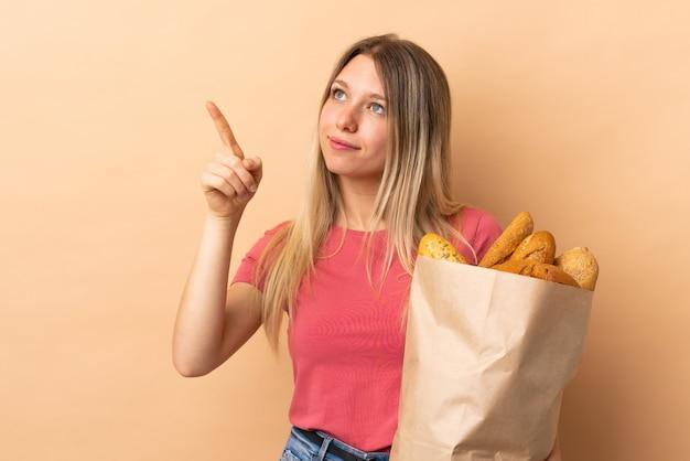 Giovane donna bionda che giudica una borsa piena di pani isolati sulla parete beige che tocca sullo schermo trasparente