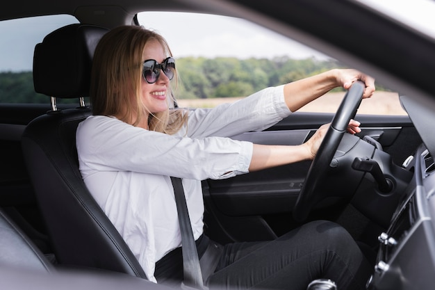 Giovane donna bionda che guida un'automobile