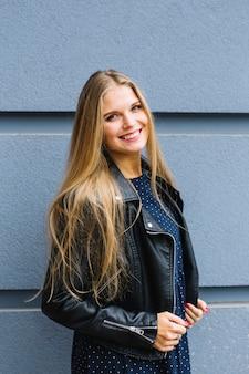 Giovane donna bionda che indossa giacca di pelle nera in piedi davanti al muro