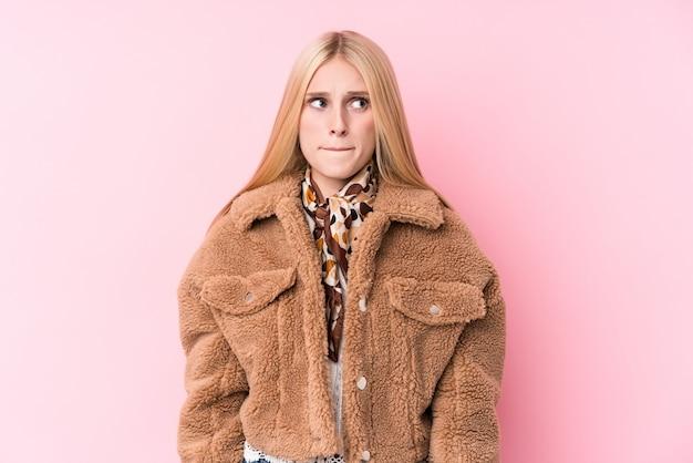 Giovane donna bionda che indossa un cappotto contro un muro rosa confuso, si sente dubbioso e incerto.
