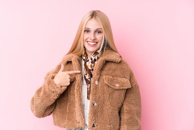 Giovane donna bionda che indossa un cappotto contro una persona di muro rosa che punta a mano verso uno spazio di copia camicia, orgoglioso e fiducioso