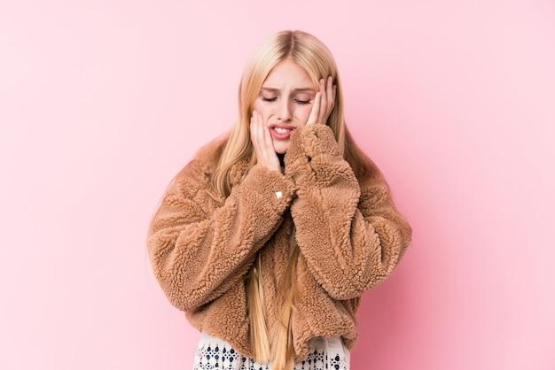 Giovane donna bionda che indossa un cappotto rosa piagnucolando e piangendo sconsolato.