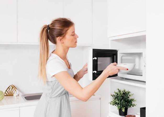 Giovane donna bionda che inserisce la ciotola nel forno