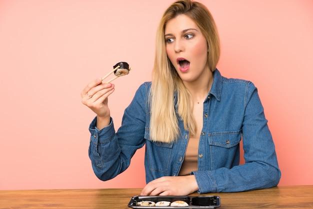 Giovane donna bionda che mangia i sushi