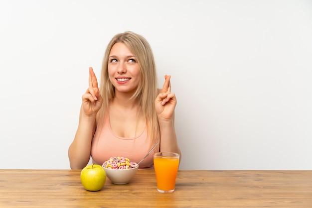 Giovane donna bionda che mangia prima colazione con l'incrocio delle dita