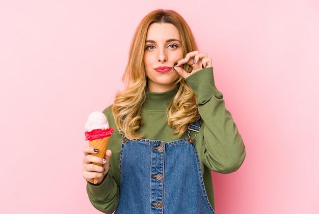 Giovane donna bionda che mangia un gelato con le dita sulle labbra mantenendo un segreto.