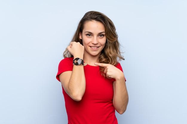 Giovane donna bionda che mostra l'orologio a mano