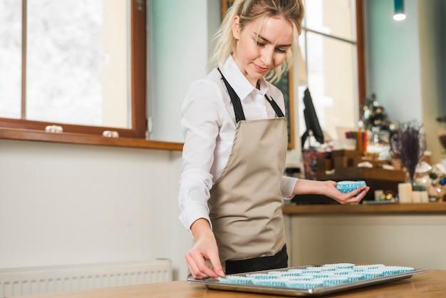 Giovane donna bionda che organizza le tazze di silicone blu per cupcakes o muffin sul vassoio