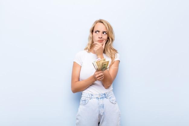 Giovane donna bionda che pensa, si sente dubbiosa e confusa, con diverse opzioni, chiedendosi quale decisione prendere con le banconote in dollari