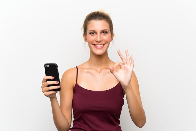 Giovane donna bionda che per mezzo del telefono cellulare che mostra un segno giusto con le dita