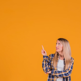 Giovane donna bionda che punta il dito verso l'alto cercando contro uno sfondo arancione