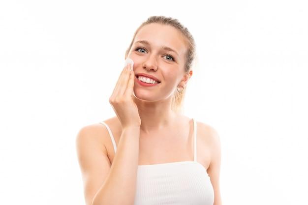 Giovane donna bionda che rimuove trucco dal suo fronte con un batuffolo di cotone