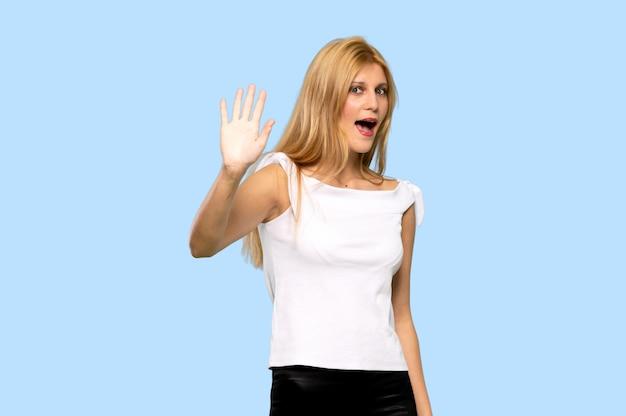 Giovane donna bionda che saluta con la mano con l'espressione felice su fondo blu isolato
