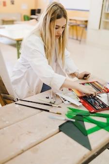 Giovane donna bionda che sceglie matita colorata dalla scatola