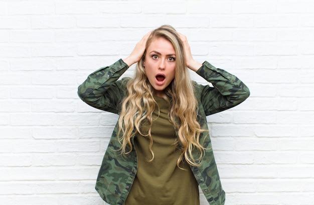 Giovane donna bionda che sembra eccitata e sorpresa, a bocca aperta con entrambe le mani sulla testa, sentendosi come un fortunato vincitore su sfondo di muro di mattoni