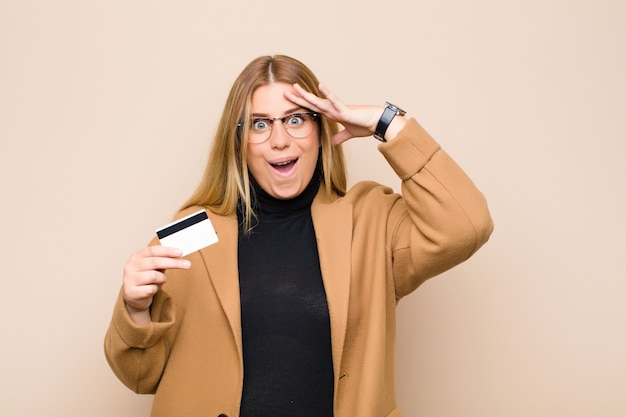 Giovane donna bionda che sembra felice, stupita e sorpresa, sorridente e realizzando sorprendenti e incredibili buone notizie con una carta di credito