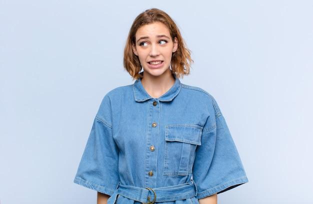 Giovane donna bionda che sembra preoccupata, stressata, ansiosa e spaventata, in preda al panico e stringendo i denti contro la parete di colore piatto