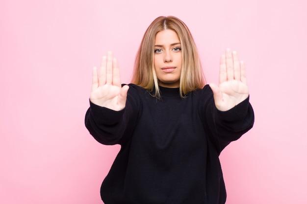 Giovane donna bionda che sembra seria, infelice, arrabbiata e scontenta di vietare l'ingresso o di dire basta con entrambi i palmi aperti contro la parete piatta