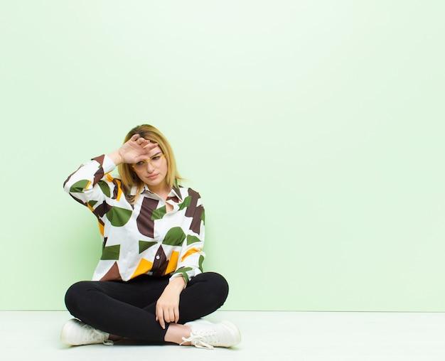 Giovane donna bionda che sembra stressata, stanca e frustrata, asciuga il sudore dalla fronte, si sente senza speranza ed esausta seduta sul pavimento