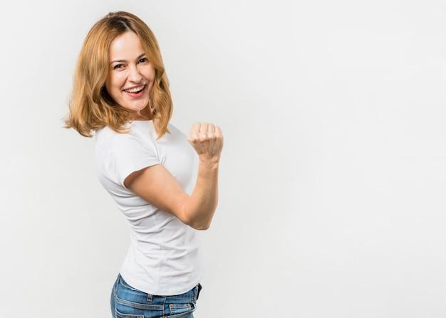 Giovane donna bionda che serra il suo pugno che si leva in piedi contro la priorità bassa bianca