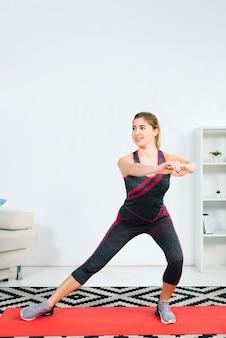Giovane donna bionda che si esercita allungando esercizio a casa