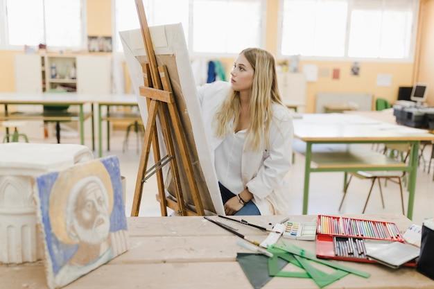 Giovane donna bionda che si siede nella pittura dell'officina sul cavalletto