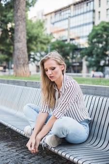 Giovane donna bionda che si siede sul banco con le gambe incrociate nel parco