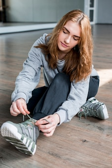 Giovane donna bionda che si siede sul pavimento di legno duro che lega laccetto