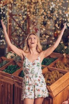 Giovane donna bionda che sta davanti alla cassa di legno che alza il suo braccio ha sollevato cercare