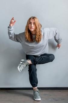 Giovane donna bionda che sta su un piede contro la parete grigia