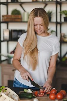 Giovane donna bionda che taglia i pomodori rossi con il coltello affilato