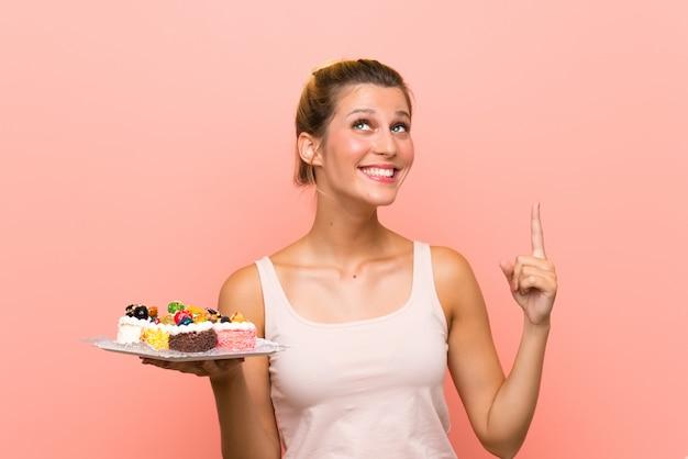 Giovane donna bionda che tiene i lotti di mini torte differenti che intendono