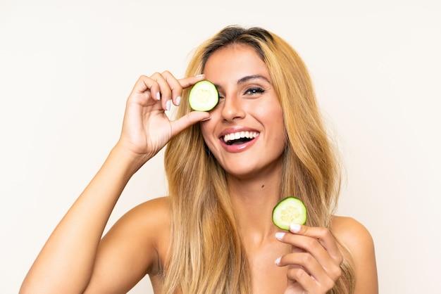Giovane donna bionda che tiene le fette di cetriolo