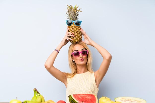 Giovane donna bionda che tiene un ananas con gli occhiali da sole