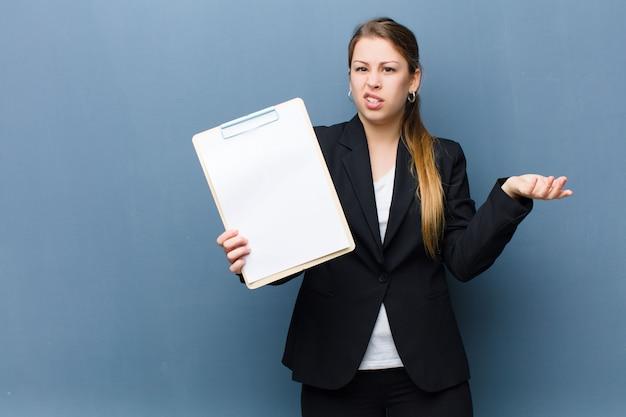 Giovane donna bionda che tiene un'insegna dello strato di carta contro il fondo della parete di lerciume