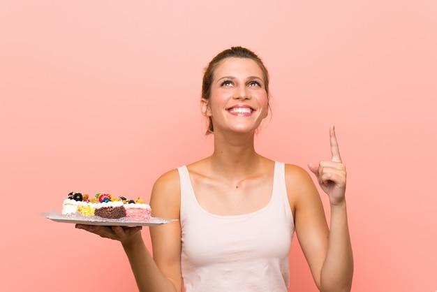 Giovane donna bionda che tiene un sacco di diverse mini torte che indicano una grande idea