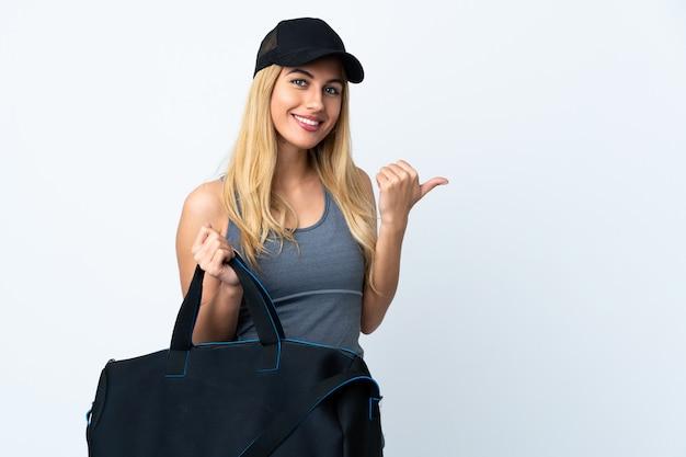 Giovane donna bionda che tiene una borsa di sport sopra la parete bianca isolata che indica il lato per presentare un prodotto