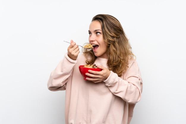 Giovane donna bionda che tiene una ciotola di cereali