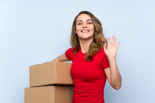 Giovane donna bionda che tiene una scatola per spostarla in un altro sito e salutare