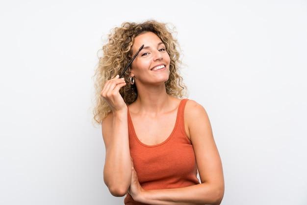 Giovane donna bionda con capelli ricci che applica mascara con attività cosmetica