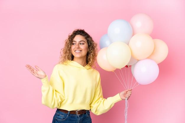 Giovane donna bionda con capelli ricci che cattura molti palloni sulla parete rosa che estende le mani al lato