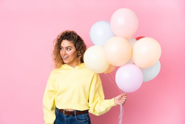 Giovane donna bionda con capelli ricci che cattura molti palloni sulla parete rosa che guarda al lato